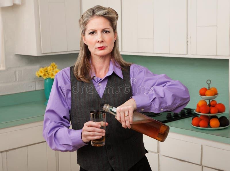Vrouw die in belemmering een drank giet stock afbeeldingen