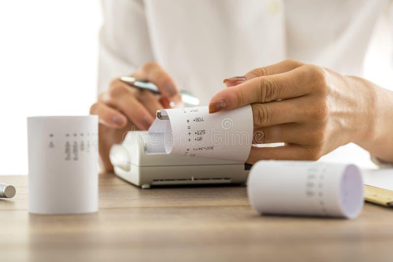 Vrouw die berekeningen op een rekenmachine doen stock foto's