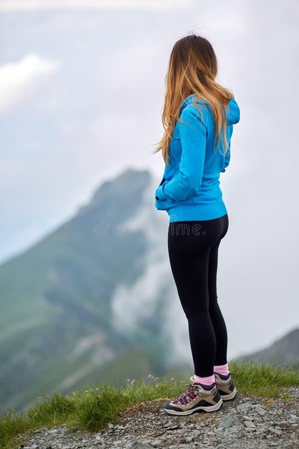 Vrouw die berg hoogste uitzicht overwegen royalty-vrije stock afbeeldingen