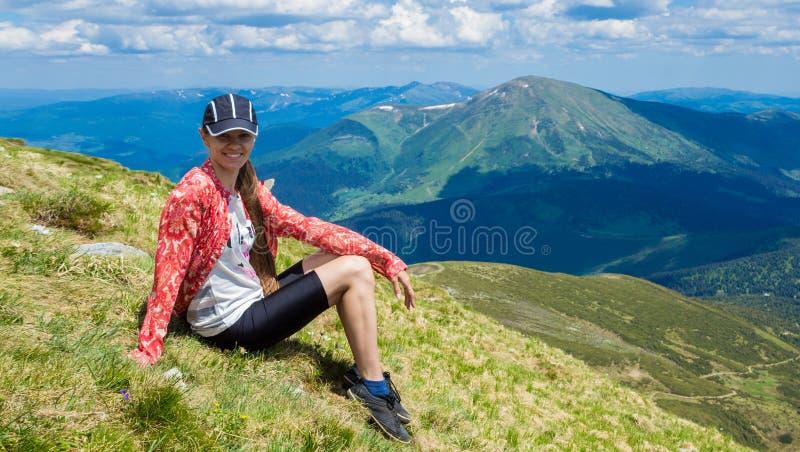 Vrouw die in bergen bij zonnige dag wandelen stock foto's