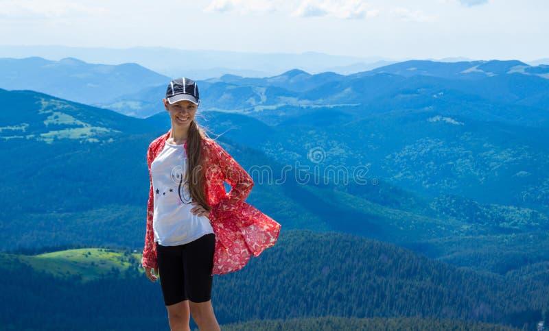 Vrouw die in bergen bij zonnige dag wandelen stock afbeelding