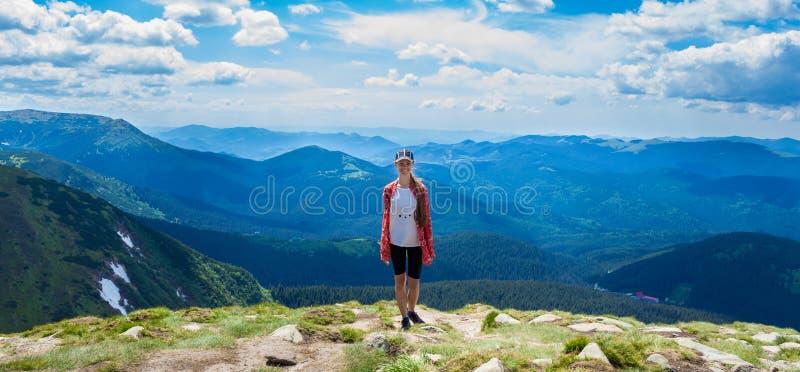Vrouw die in bergen bij zonnige dag wandelen royalty-vrije stock fotografie