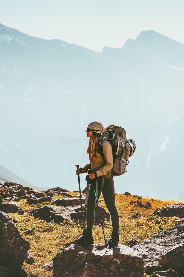 Vrouw die in bergen reizen die met rugzak wandelen stock foto's