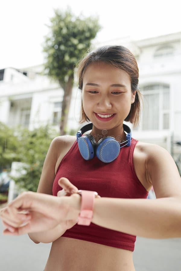 Vrouw die berichten controleren op haar slim horloge stock foto