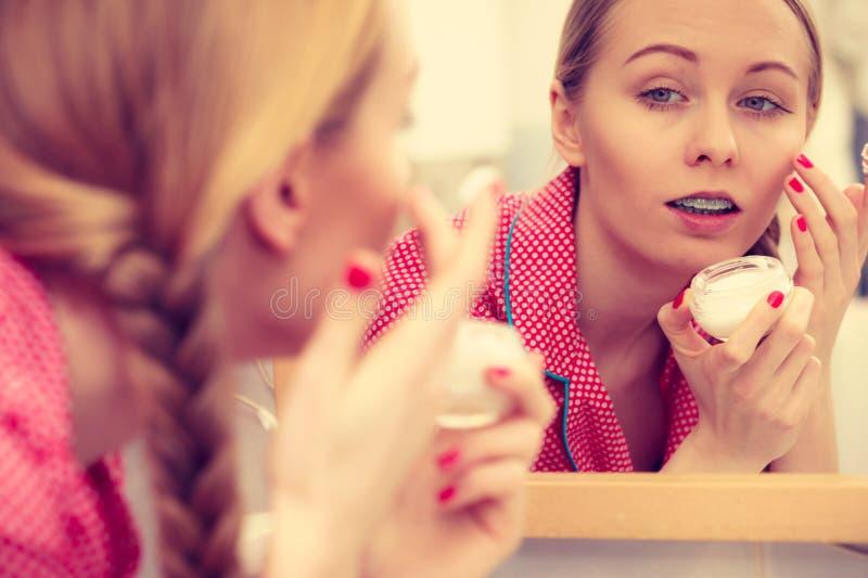 Vrouw die bevochtigende huidroom toepassen Skincare stock afbeeldingen