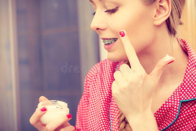 Vrouw die bevochtigende huidroom toepassen Skincare stock afbeelding