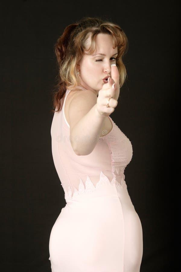 Vrouw die beweert een kanon te ontspruiten dat haar hand gebruikt stock fotografie