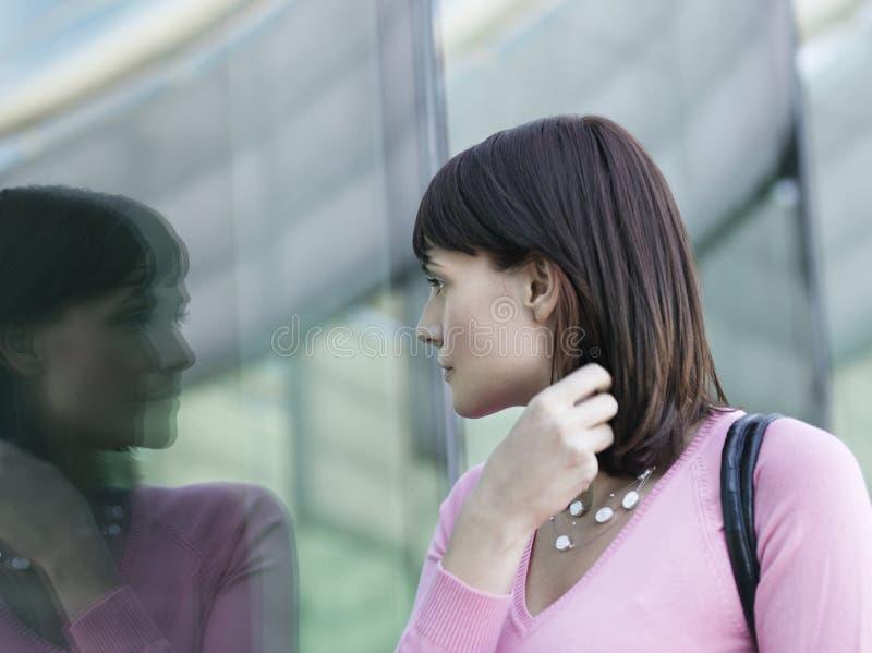 Vrouw die Bezinning van Zelf in Venster bekijken stock fotografie