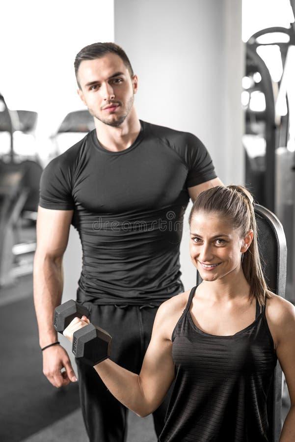 Vrouw die bicep krullen in gymnastiek met haar persoonlijke trainer doen stock foto