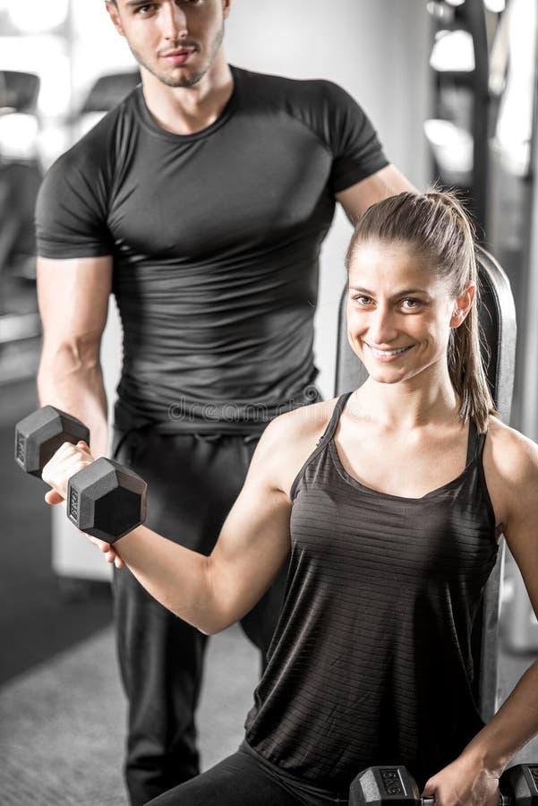 Vrouw die bicep krullen in gymnastiek met haar persoonlijke trainer doen royalty-vrije stock fotografie