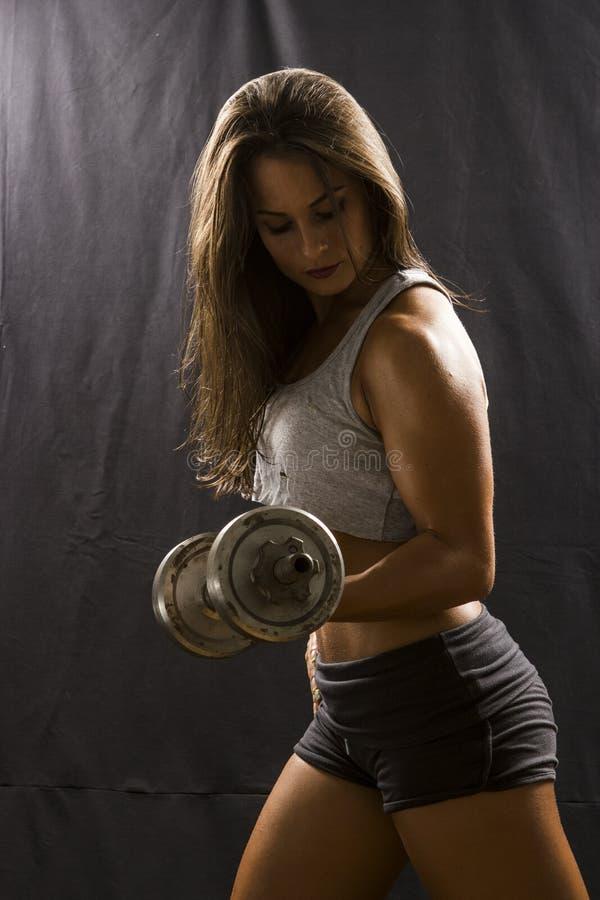 Vrouw die bicepsenkrul met domoor doen royalty-vrije stock foto's