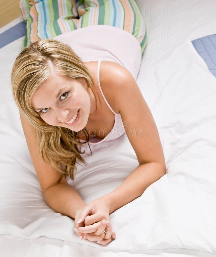 Vrouw die bij bed en het glimlachen legt royalty-vrije stock fotografie
