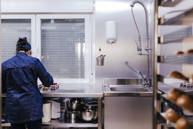 Vrouw die bij de bakkerij werkt die snoepjes voorbereidt royalty-vrije stock afbeelding