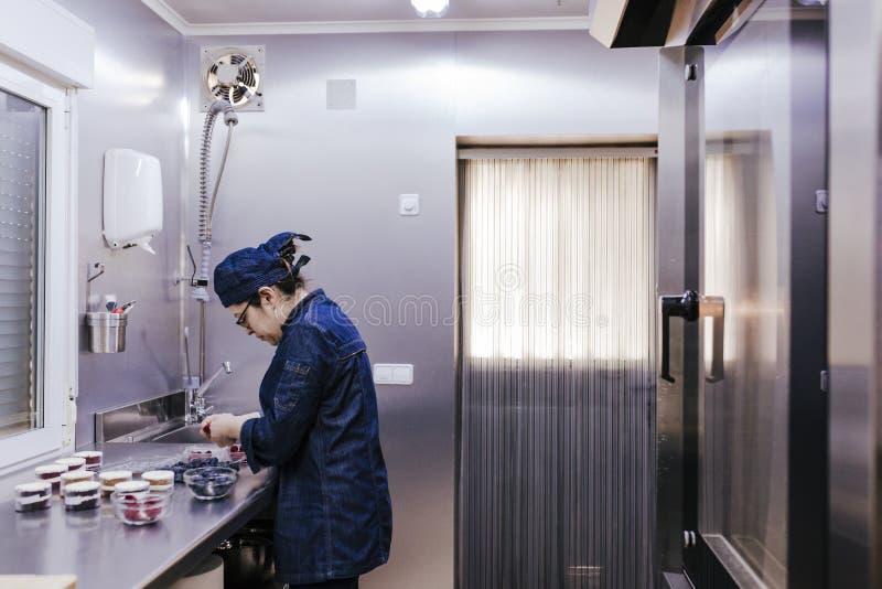 Vrouw die bij de bakkerij werkt die snoepjes voorbereidt royalty-vrije stock fotografie