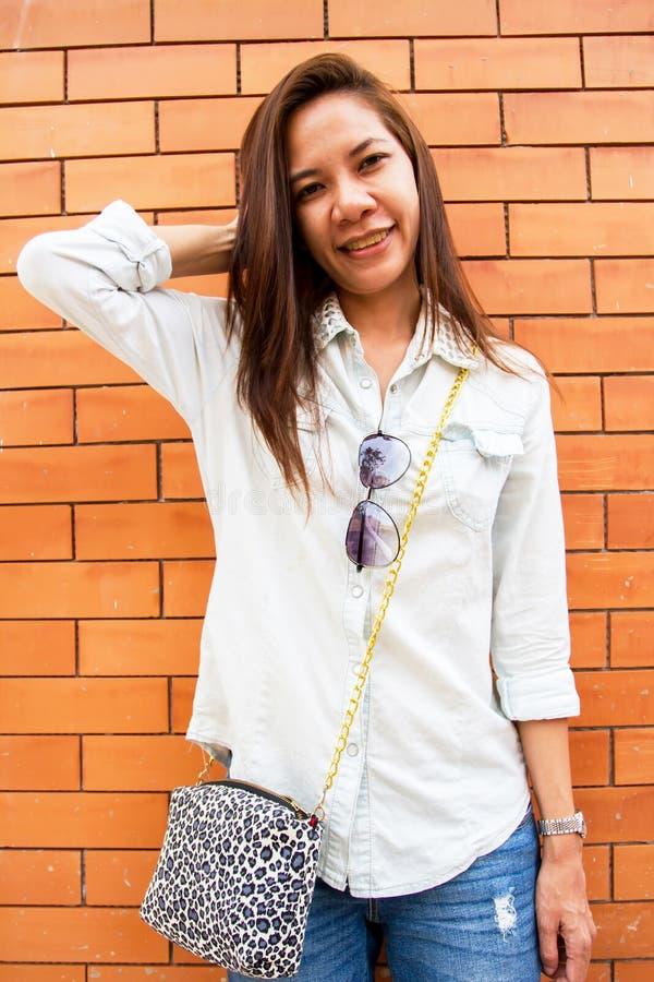 Vrouw die bij de bakstenen muurachtergrond glimlachen royalty-vrije stock afbeelding