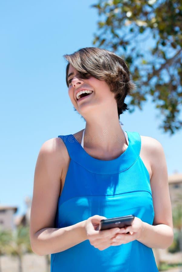 Vrouw die bij de inhoud van lachen sms stock afbeeldingen