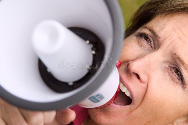 Vrouw die bij de megafoon schreeuwt stock foto's