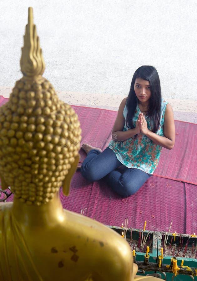 Vrouw die bij een standbeeld van Boedha bidden royalty-vrije stock afbeelding