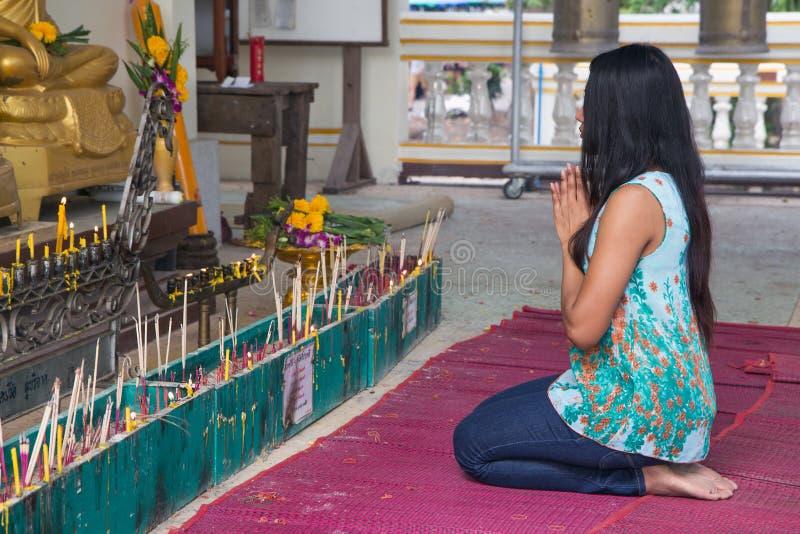 Vrouw die bij een standbeeld van Boedha bidden stock foto's