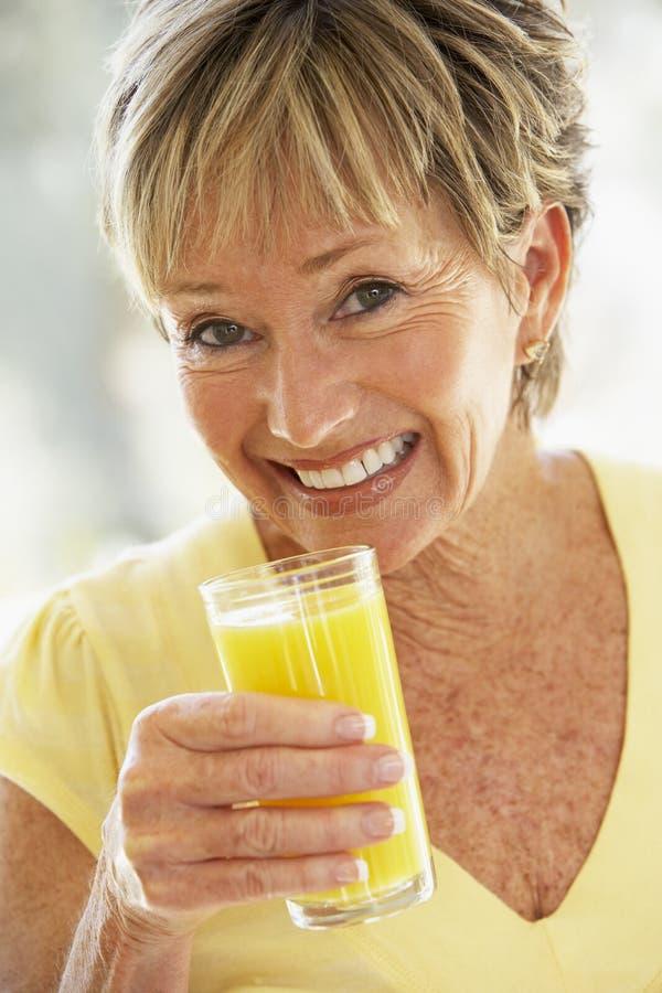 Vrouw die bij het Drinken van de Camera Jus d'orange glimlacht royalty-vrije stock afbeeldingen
