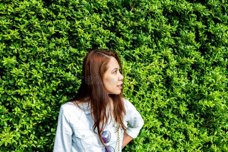Vrouw die bij het park tegen de achtergrond van groen blad glimlachen stock foto