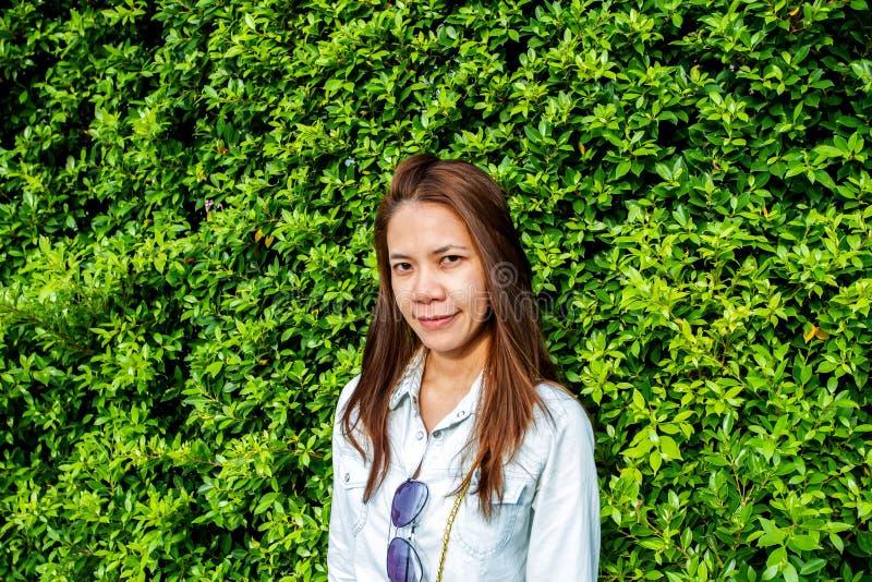 Vrouw die bij het park tegen de achtergrond van groen blad glimlachen stock afbeelding