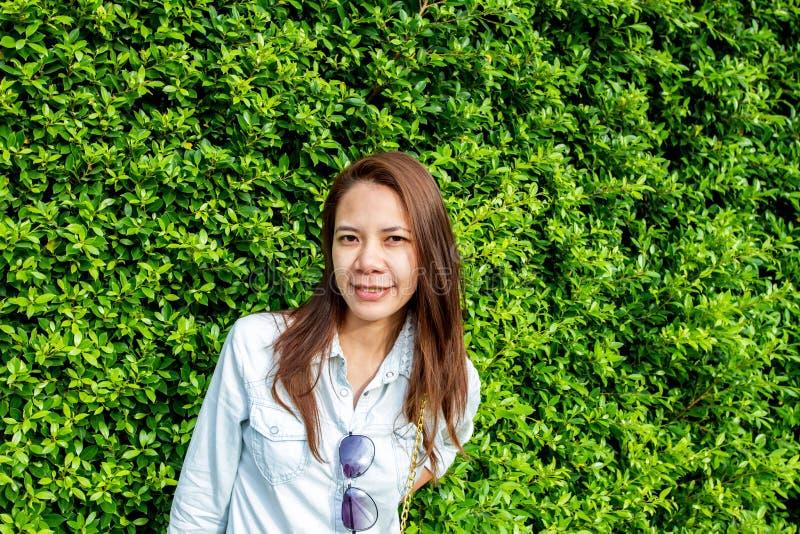 Vrouw die bij het park tegen de achtergrond van groen blad glimlachen royalty-vrije stock foto's
