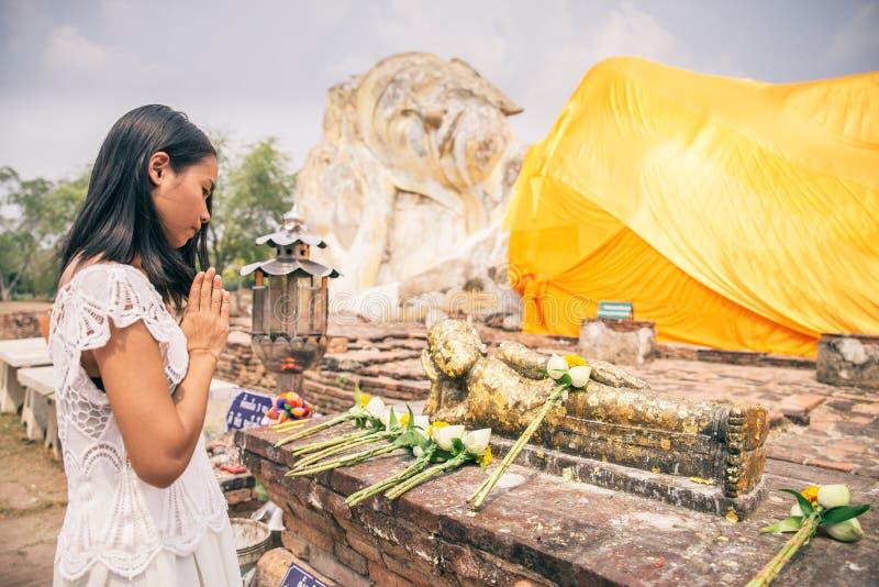 Vrouw die bij het standbeeld van Boedha bidden royalty-vrije stock afbeeldingen