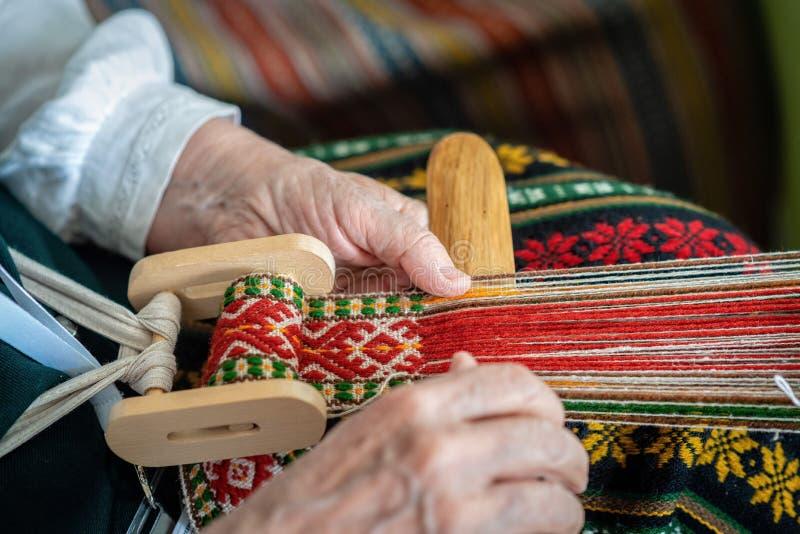 Vrouw die bij het wevende weefgetouw werken Traditionele Etnische ambacht van de Oostzee - Beeld stock afbeelding
