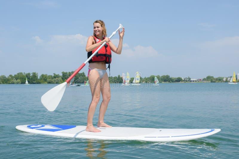 Vrouw die bij het windsurfing van de roeispaan van de raadsholding wordt bevonden stock fotografie