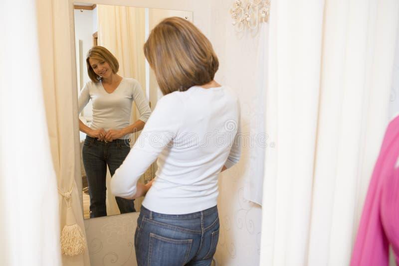 Vrouw die bij jeans en het glimlachen probeert stock foto's