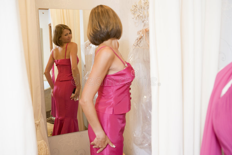 Vrouw die bij kleding en het fronsen probeert stock afbeelding