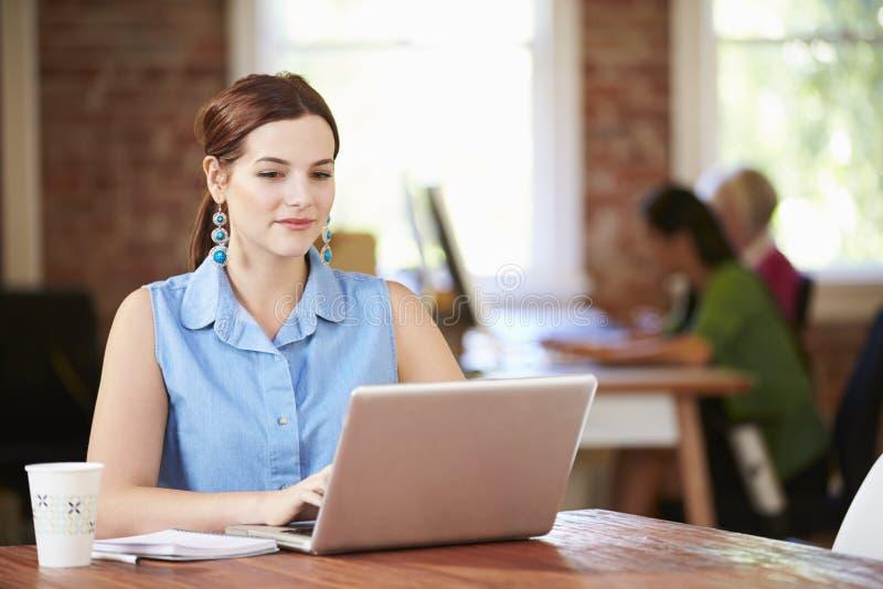 Vrouw die bij Laptop in Eigentijds Bureau werken royalty-vrije stock afbeeldingen