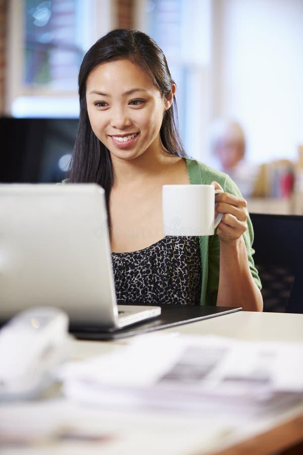 Vrouw die bij Laptop in Eigentijds Bureau werken stock afbeeldingen