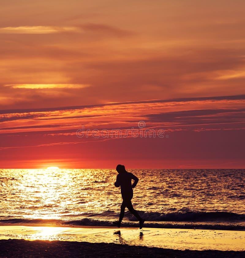 Vrouw die bij mooie zonsondergang in het strand lopen royalty-vrije stock fotografie