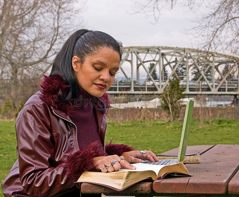 Vrouw die bij Park met Laptop Computer bestudeert stock afbeelding