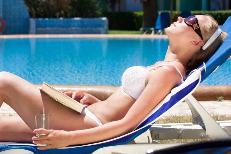 Vrouw die bij pool rust stock afbeeldingen
