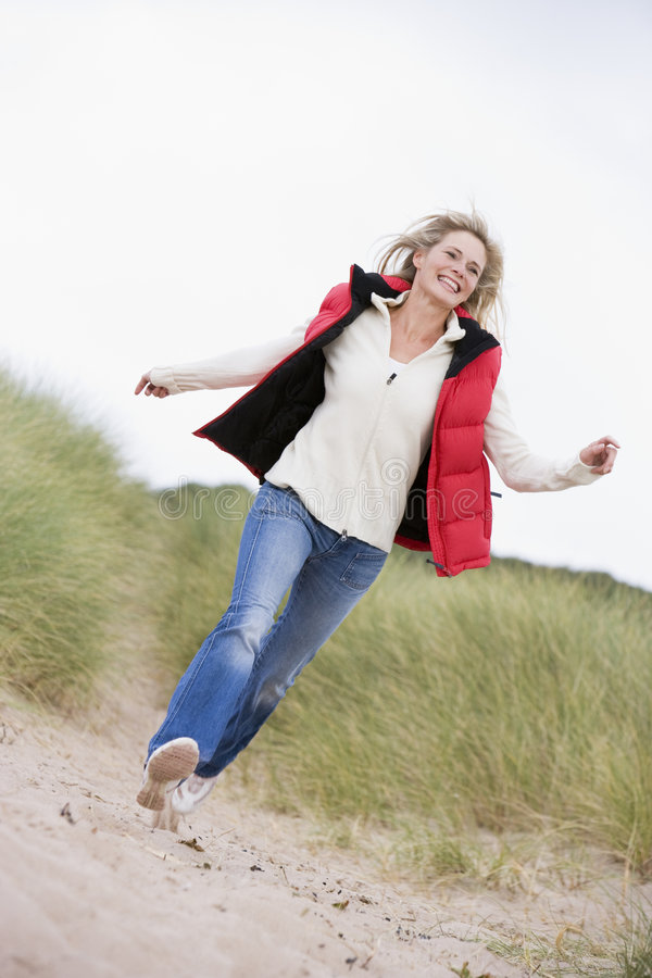 Vrouw die bij strand het glimlachen loopt royalty-vrije stock fotografie
