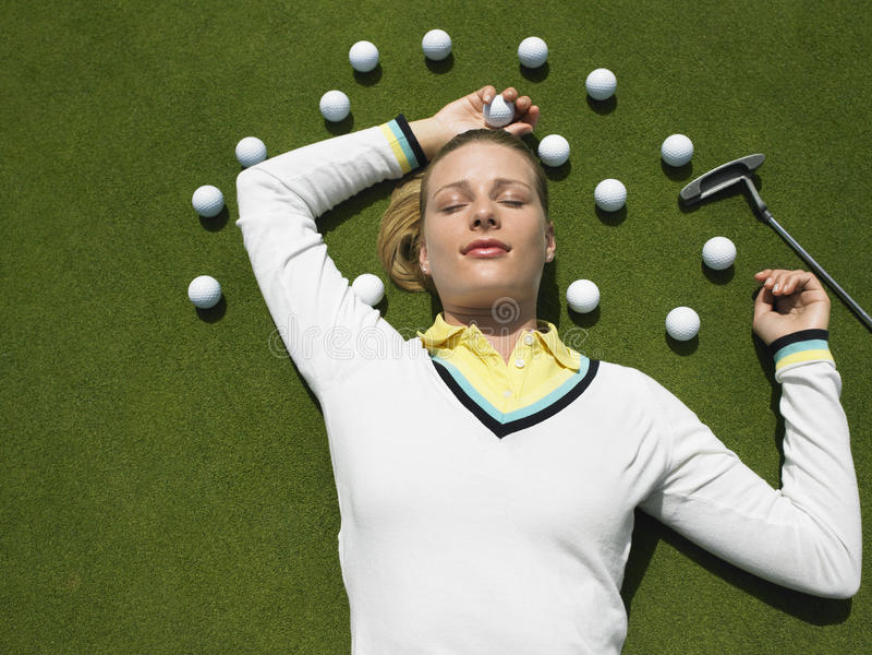 Vrouw die bij Zetten liggen Groen met Golfballen royalty-vrije stock foto