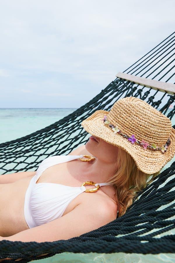 Vrouw die Bikini en Zonhoed het Ontspannen in Strandhangmat dragen royalty-vrije stock afbeeldingen