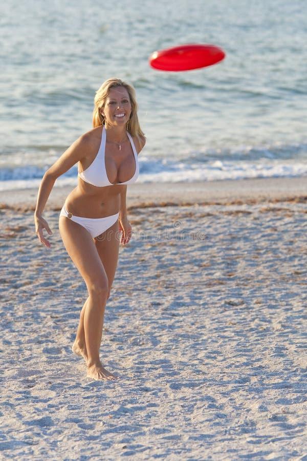 Vrouw die in Bikini Frisbee speelt bij een Strand royalty-vrije stock foto's