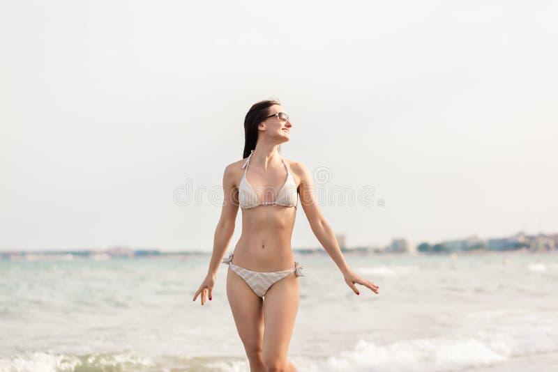 Vrouw die in bikini onderaan het strand in haar de zomervakantie lopen stock foto's