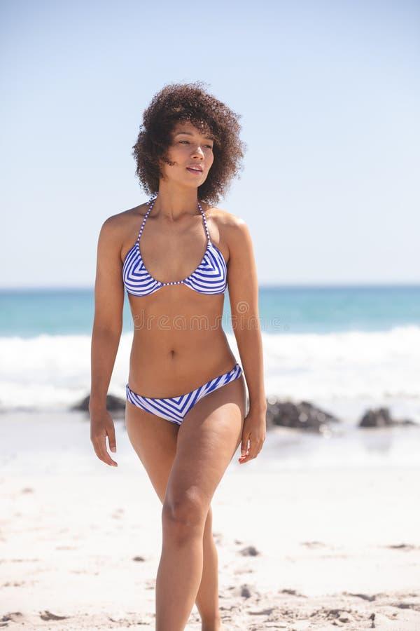 Vrouw die in bikini op het strand lopen stock foto