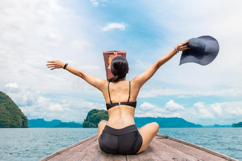 Vrouw die bikinizitting op de boot met handen omhoog en holding dragen beachhat royalty-vrije stock foto's