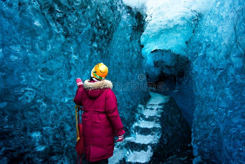 Vrouw die blauw ijshol in IJsland onderzoeken stock afbeeldingen