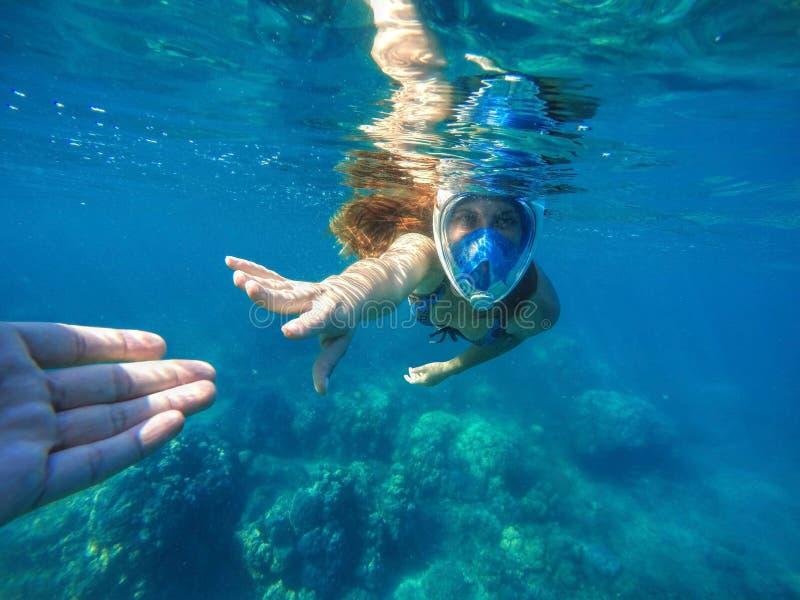 Vrouw die in blauw masker dichtbij koraalrif snorkelen stock foto