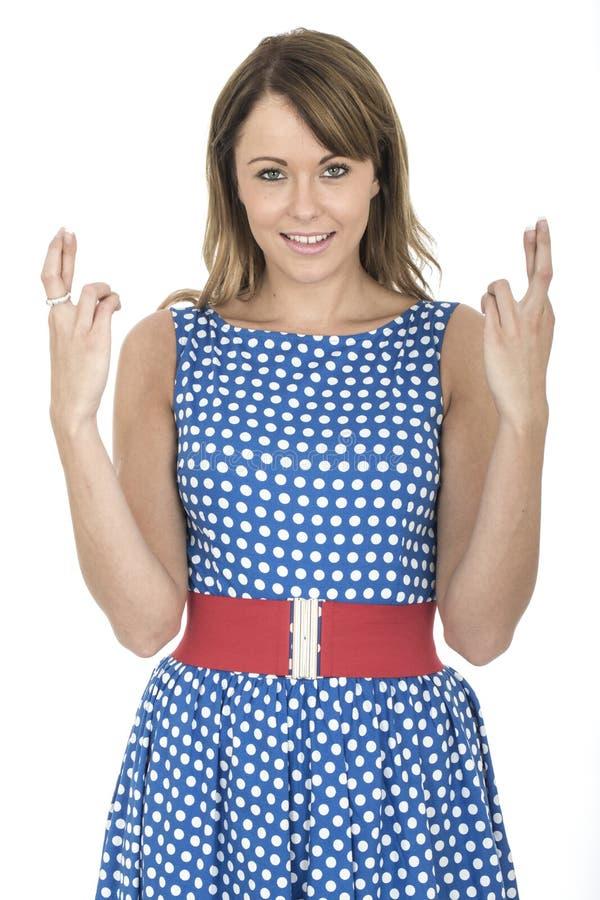 Vrouw die Blauwe Polka Dot Dress Fingers Crossed dragen royalty-vrije stock fotografie