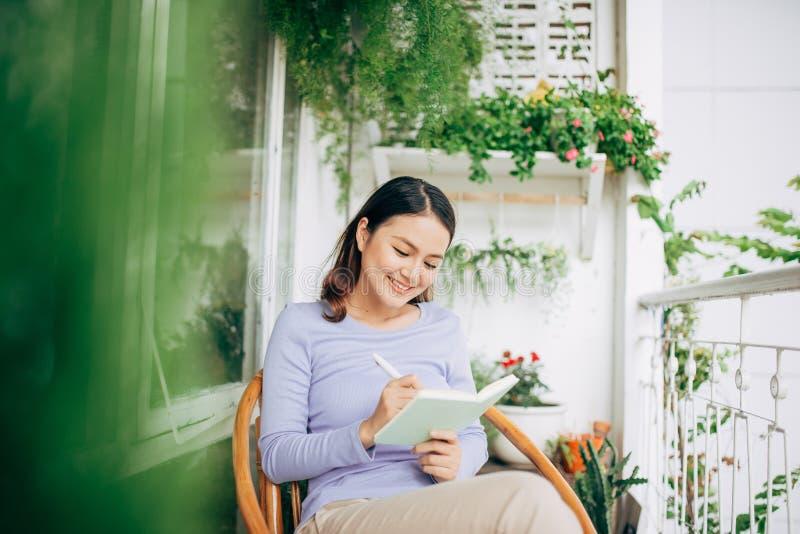 Vrouw die in blocnote schrijven die op witte moderne stoel thuis wordt geplaatst, freelancer royalty-vrije stock afbeelding