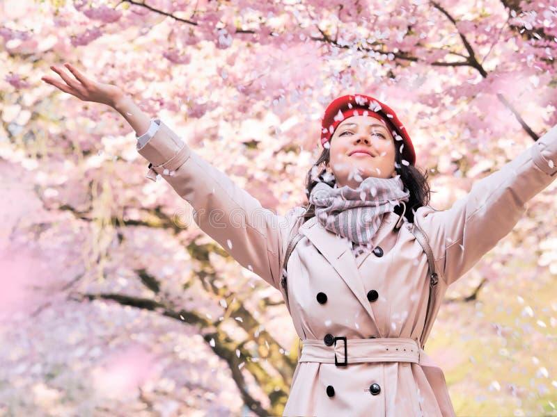 Vrouw die bloembloemblaadjes werpen die van een bloeiende de lentetuin genieten royalty-vrije stock foto