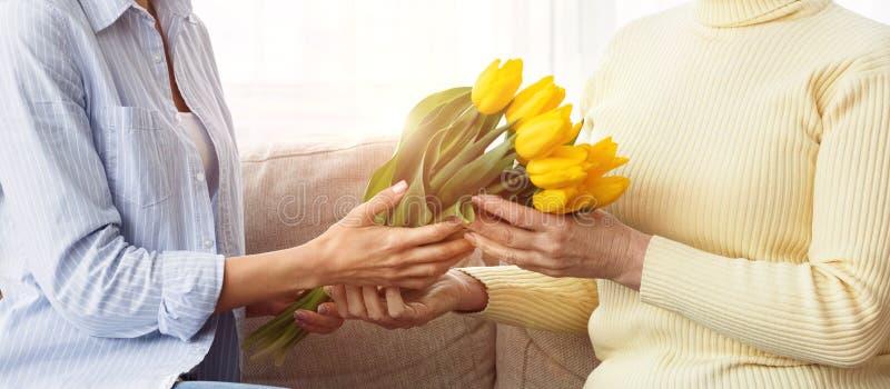 Vrouw die bloemen geven aan haar rijpe moeder royalty-vrije stock fotografie